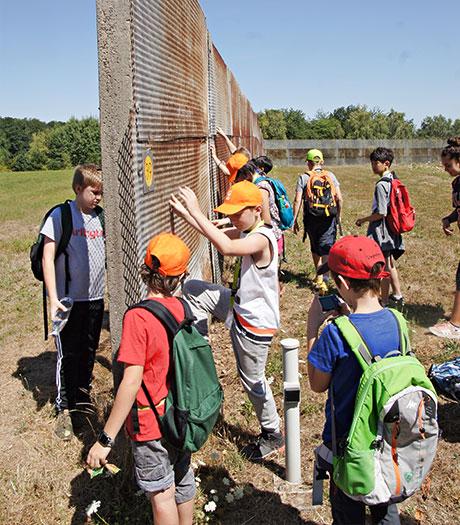 Schüler vor Überbleibseln des Grenzzauns