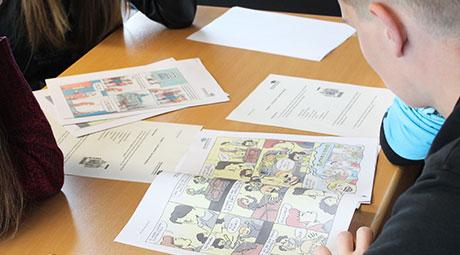 Schüler lesen ein Comic in einer Gruppenarbeit