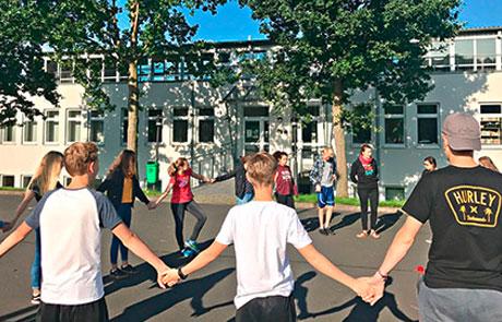 Schüler halten sich an den Händen und bilden einen Kreis