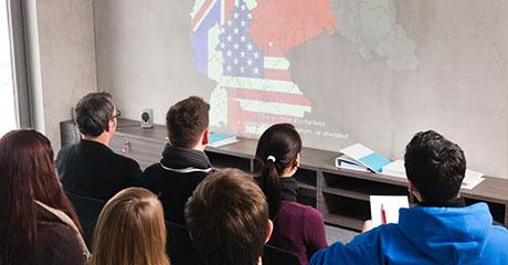 Schüler schauen einen Vortrag an der Leinwand